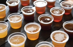 A table of beer samples in plastic cups